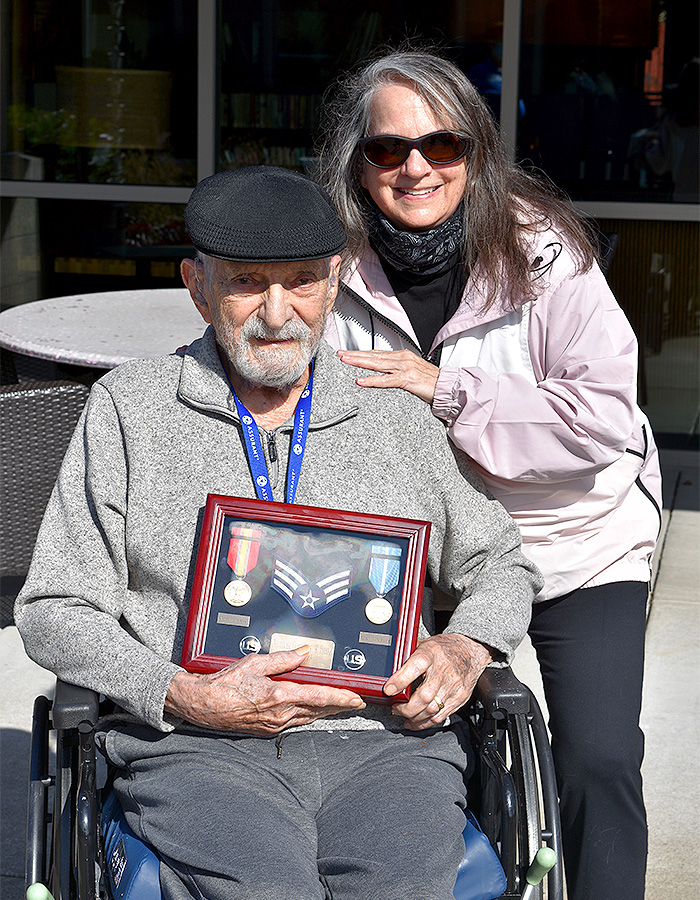 VCCO Employee smiling with veteran who is holding their medals